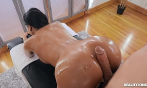 Tanned brunette with fake tits banged by her masseur